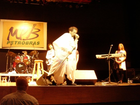 Tom Zé in 2008 performing in front of a Petrobras sign, photo used by CC license, Neto Silveira