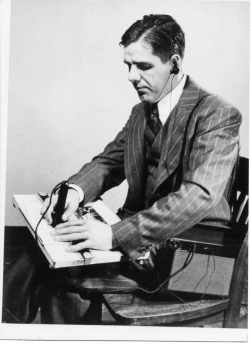 Piechowski, wearing a suit, scans the pen of the A-2 reader over a document.