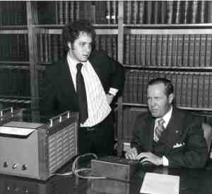 A young Kurzweil stands by his reading machine, demonstrated by Jernigan, who is seated.