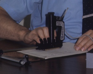 Lauer's fingers are pictured in the finger-rests of the Visotactor, scanning a document.