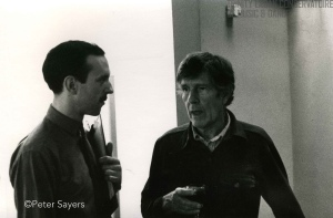 """Photograph of John Cage talking to another guest at a drinks reception at the Cage/Cunningham Residency at the Laban Centre, Laurie Grove, London, July 1980"" by Flickr user Laban Archive,"