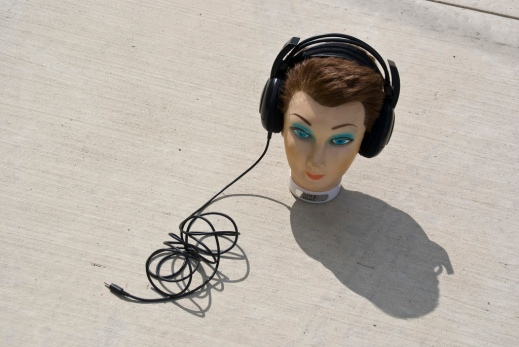 """mannequin head on concrete with headphones"" from Flickr user J E Theriot, (CC BY 2.0)"