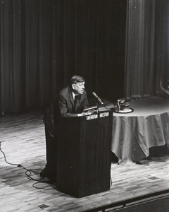Photograph of Auden speaking at the Boston Sheraton Hotel, with Professor John L. Mahoney sitting on stage, February 23, 1966, Box 60, Folder 9, Francis W. Sweeney, SJ, Humanities Series Director's Records, MS2002-37, John J. Burns Library, Boston College.