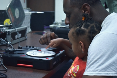 A black man plays with a turntable, with his daughter in his lap